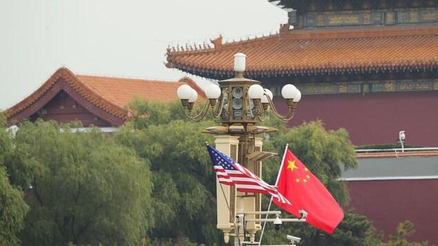 Des drapeaux des États-Unis et de la Chine flottent côte à côte dans un quartier de Pékin.