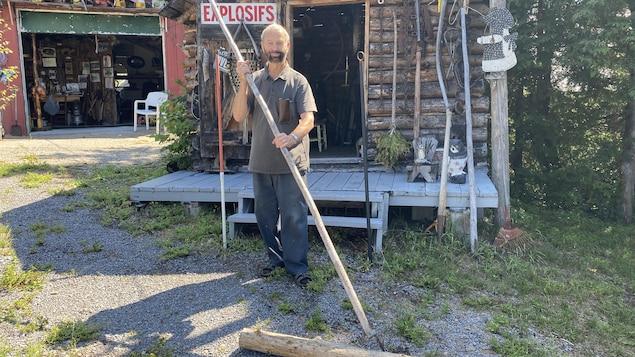Un homme tenant une gaffe à la main pose devant une cabane en bois rond.