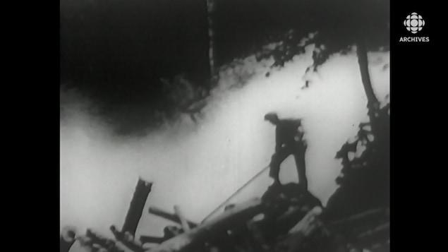 Un draveur, avec sa gaffe, est perché sur des billots au bas d'une chute d'eau.