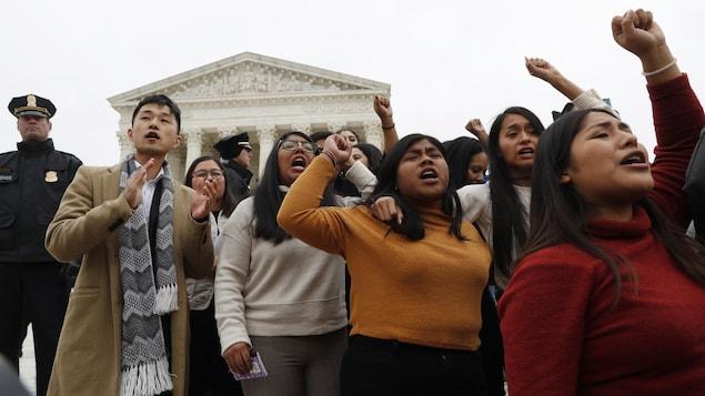 Des manifestants, plusieurs ayant le poing en l'air, se tiennent debout devant la Cour suprême.