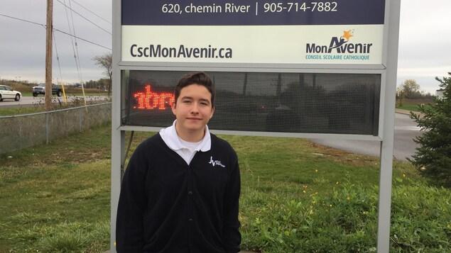 Drew devant le panneau de l'école