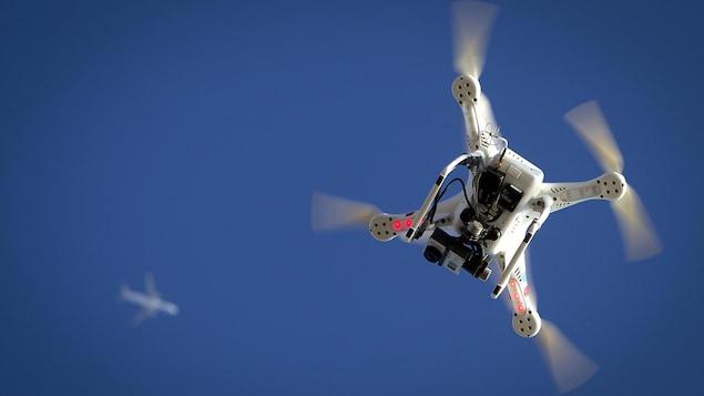 Un drone vole au-dessous d'un avion.