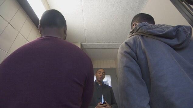 Deux jeunes hommes de dos devant le journaliste de CBC News