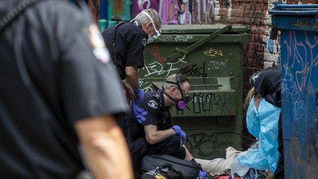 Des ambulanciers tentent de réanimer une personne victime d'une surdose dans le quartier du Downtown Eastside à Vancouver le 11 mai 2020.