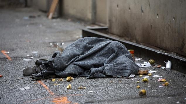 Un homme allongé sous une couverture dans le quartier du Downtown Eastside, à Vancouver.