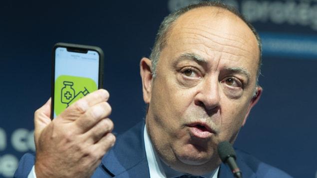 Le ministre tient un cellulaire dans la main