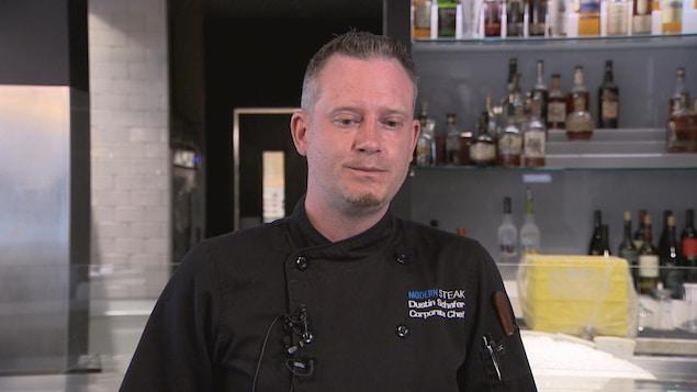 Un homme portant une tunique de cuisinier se tient debout dans un restaurant.