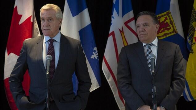 Les deux hommes, côte à côte, devant des drapeaux.