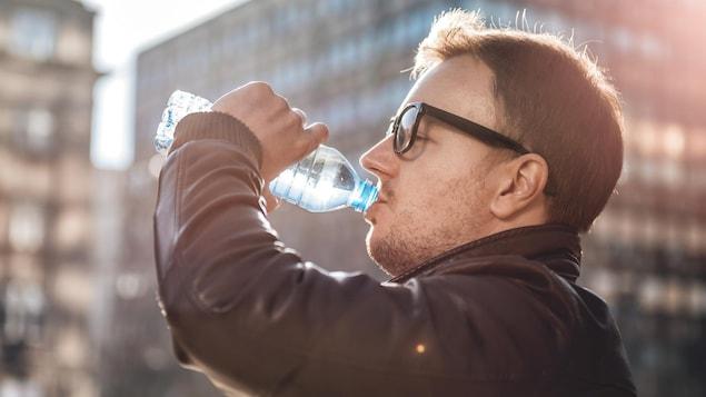 Un homme boit de l'eau dans une bouteille en plastique.
