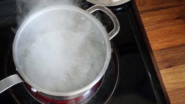 De l'eau en ébullition dans un chaudron sur une cuisinière.
