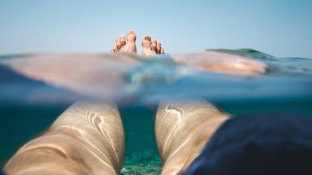 Les pieds d'un homme flottent à la surface de l'océan.