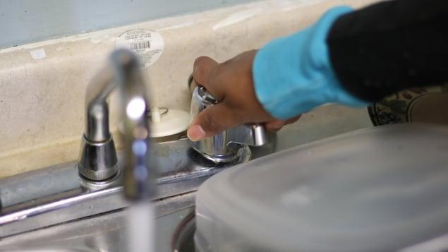 Une main de femme qui ouvre un robinet d'où coule de l'eau.