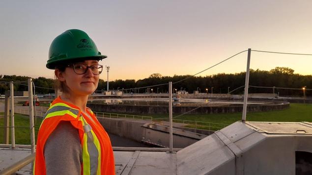 Elizabeth Mercier est devant une usine de traitement des eaux usées.