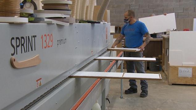 Un homme tient une planche près d'une machine.