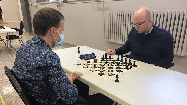 Deux hommes jouent aux échecs.