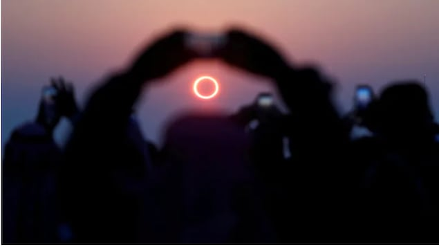 People take photos as they watch the annular solar eclipse on Jabal Arba (Four Mountains) in Hofuf, Saudi Arabia on Dec. 26, 2019.