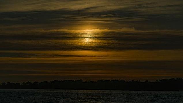 Le Soleil se lève sur le Saint-Laurent tandis que la Lune en cache une partie.
