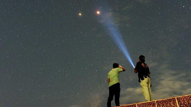 Des résidents de Padang, sur l'île de Sumatra, en Indonésie, observent l'éclipse totale de la Lune et la planète Mars à ses côtés.