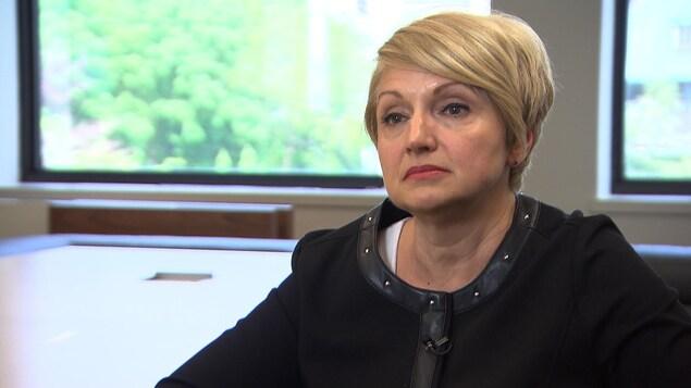 Une femme aux cheveux blonds regarde le journaliste lors d'une entrevue dans une salle de conférence devant deux grandes fenêtres.