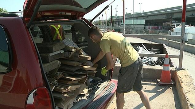 Un homme apporte des débris de construction dans un écocentre.