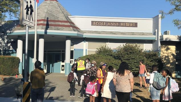 Des parents et des enfants devant l'établissement scolaire Anne Hébert.
