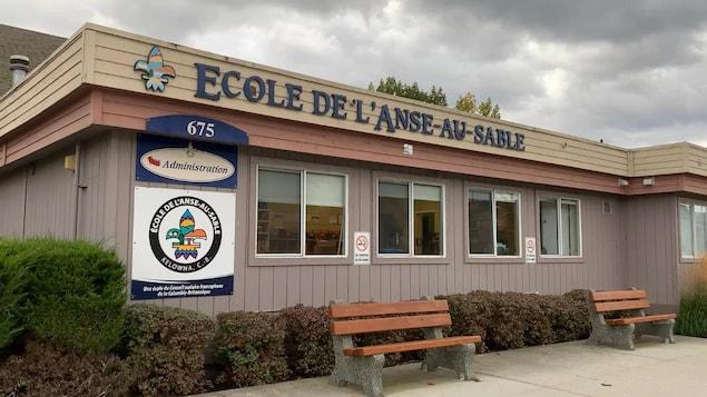 Le bâtiment de l'École de l'Anse-au-sable devant lequel se trouve deux bancs en bois.