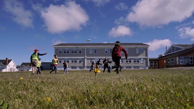 Des jeunes jouent au frisbee dans la cours de l'école St-Joseph.