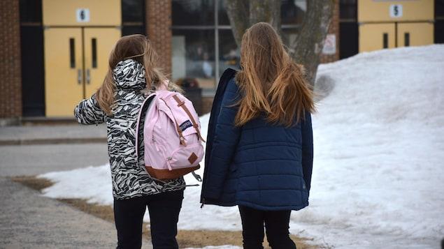 Deux élèves s'apprêtent à entrer dans l'école.