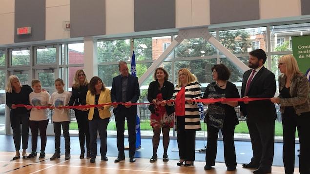 Plusieurs personnes tiennent un ruban rouge que l'on s'apprête à couper pour inaugurer la nouvelle école Baril, à Montréal.