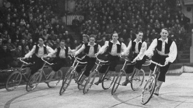 Sept artistes sur des vélos tournent en rond autour d'une piste dans un cirque