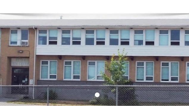 Le bâtiment de brique beige et d'un revêtement blanc est construit en longueur