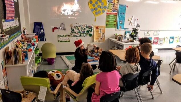 Une enseignante lit un livre à des élèves dans une salle de classe.