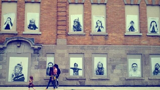 Des enfants marchent devant l'école Baril où, sur les fenêtres condamnées, des affiches montrent des écoliers qui ont du mal à respirer.