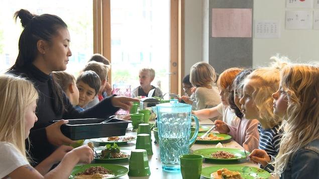 On voit une douzaine d'enfants attablés en train de prendre leur repas du midi. Une adulte est présente avec eux.