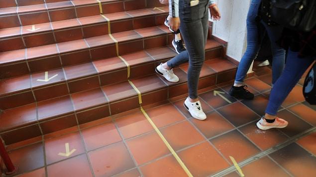 Des élèves d'une école secondaire descendent un escalier à Bonn, en Allemagne, le 12 août 2020. On ne voit que leurs jambes. Des flèches sont dessinées sur le sol avec du papier collant jaune pour diriger les gens dans une direction ou une autre.