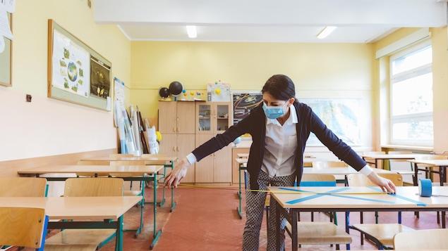 Une femme portant un masque bleu mesure la distance entre deux pupitres dans une salle de classe.