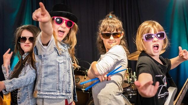Quatre jeunes filles portent des lunettes de soleil et ont les mains en l'air en chantant.