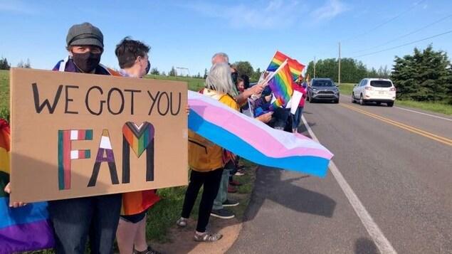 Plusieurs manifestants portent le drapeau de la Fierté, l'arc-en-ciel au bord de la route.