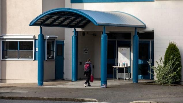 Un élève marche vers l'entrée principale d'une école.