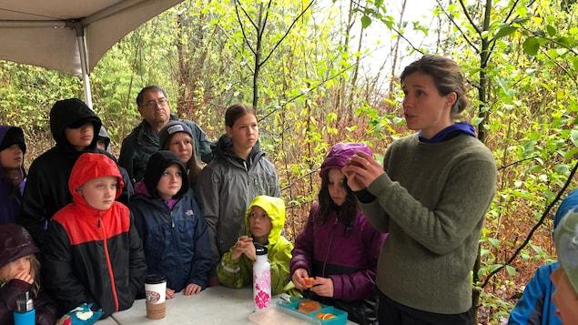 Une enseignante explique une tradition de Pâques à un groupe d'enfants.