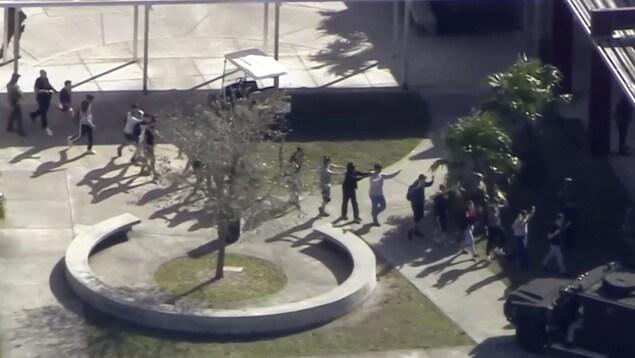 Dans cette capture d'écran fournie par WPLG-TV, des étudiants de l'école secondaire Marjory Stoneman Douglas de Parkland, en Floride, évacuent l'école après une fusillade.