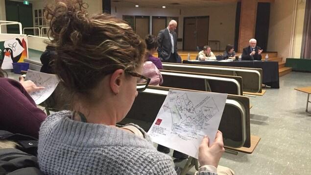 Une femme examine un plan pendant une réunion.