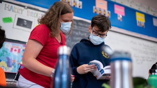 Une enseignante regarde un dictionnaire larousse avec un élève de 6e année.