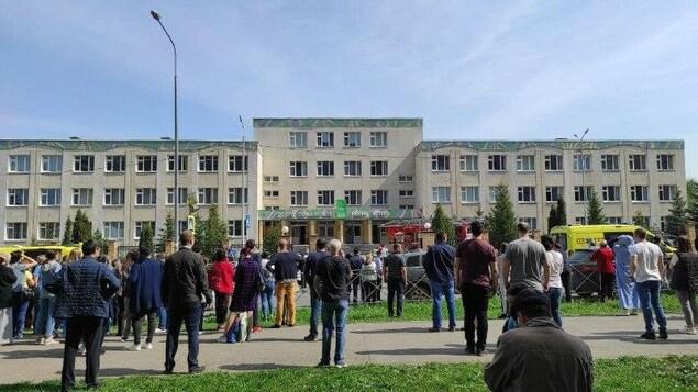 Une foule devant une école.