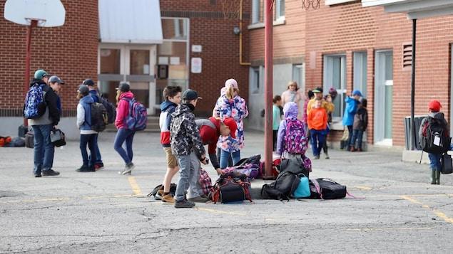 Des jeunes élèves dans une cour d'école.