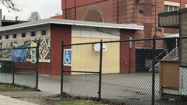 Une école en brique rouge à l'arrière-plan et à l'avant-plan, une cour d'école asphaltée et une clôture en grille métallique avec une enseigne avec le symbole d'une personne en fauteuil roulant.