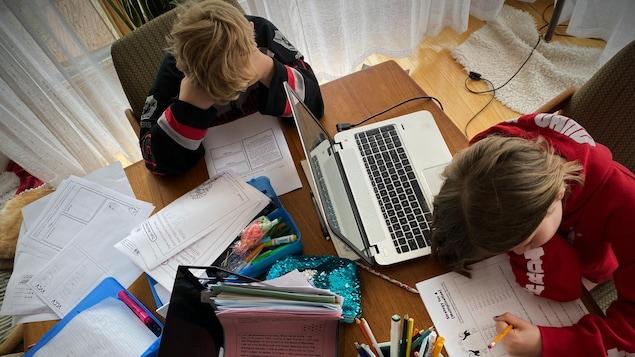 Des enfants suivent leurs cours à la maison.