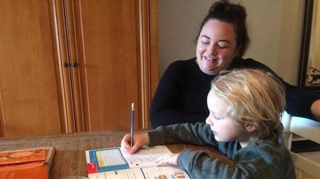 Un garçon écrit dans un cahier de mathématique sous la supervision de sa maman à la maison.