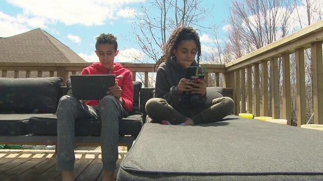 Deux enfants sont assis sur un balcon et tiennent un ordinateur portable.