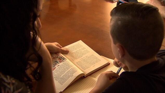 Une mère aide son fils dans ses lectures. Ils sont installés côte à côte à une table de cuisine.